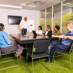 Flexible Workspace Boardroom With Table And Chairs As Well As A TV And Easle